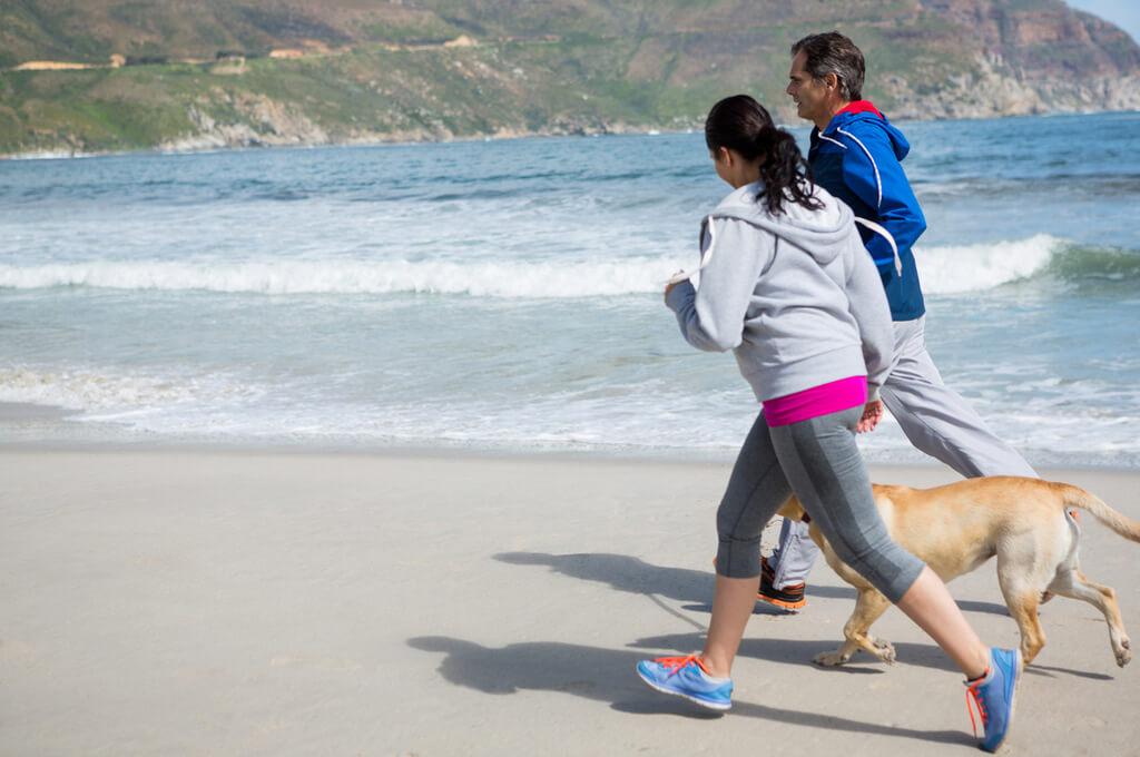 Perro corre al lado de sus dueños