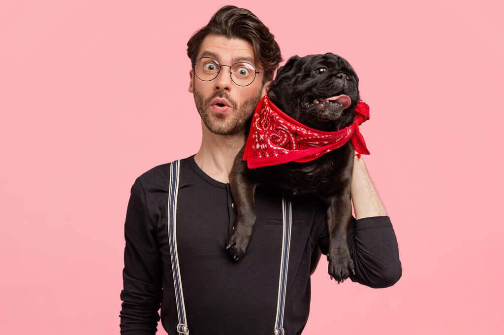 Hombre carga a su perro negro